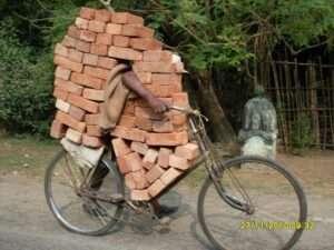 Indian riding bike & carrying bricks