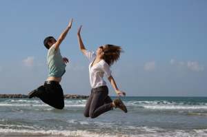 Couple Jump On Beach