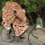 Indian riding bike & carrying bricks
